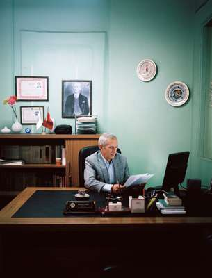 Public servant Nedim Saridag in his notary office with a photograph of Ataturk