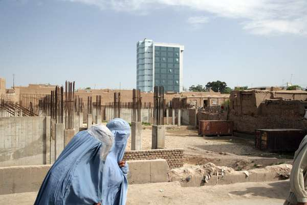 Women in traditional burqas walk past a new office block