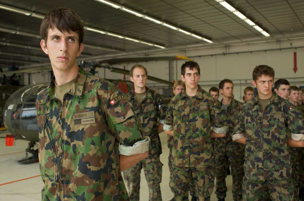Swiss conscripts receiving instructions in a military hangar at Payerne