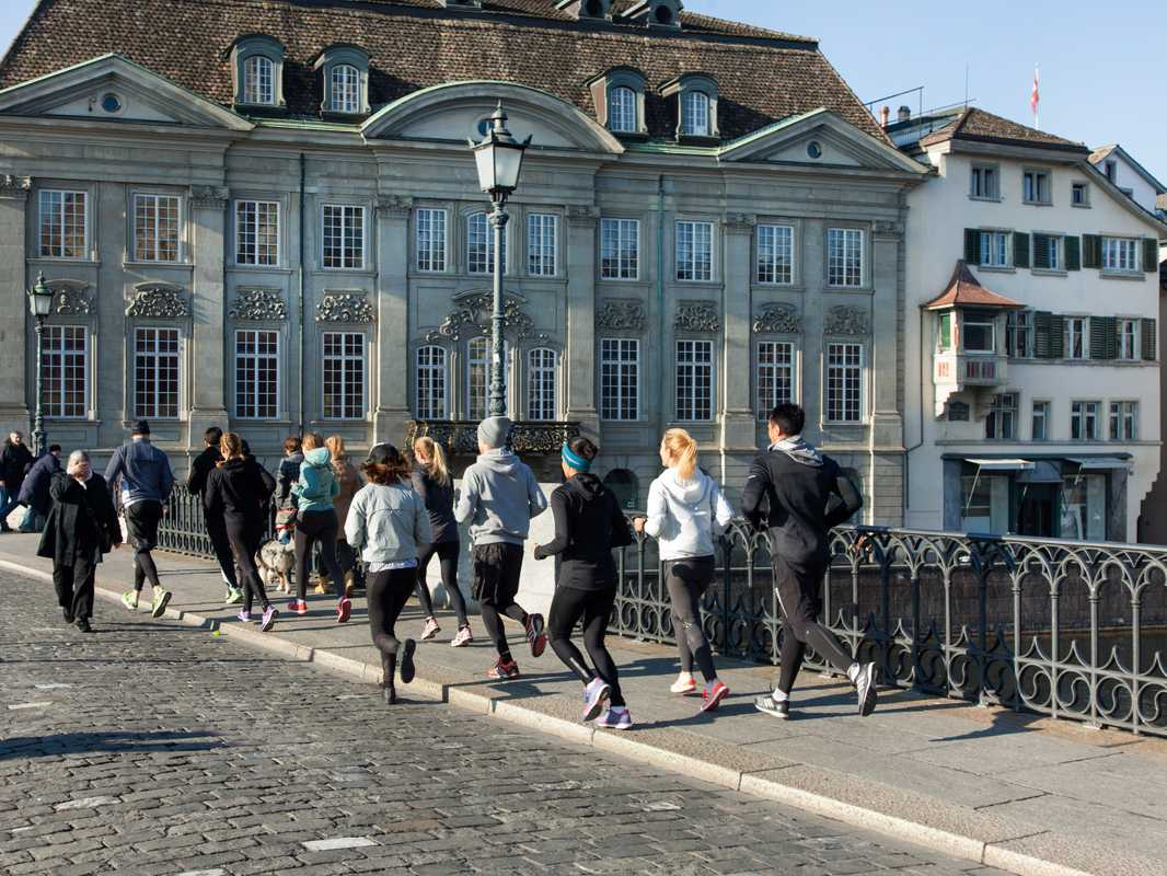 Running club crossing the Münsterbrücke in Zürich
