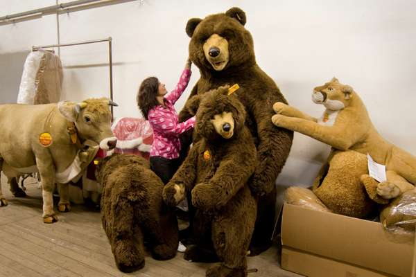 Steiff employee with a menagerie of life-size stuffed animals