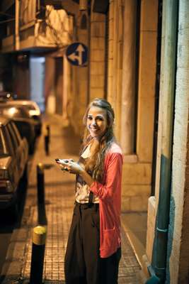 Fashion assistant Tala Hjiar sends a text outside Kayan bar, Rue de Liban