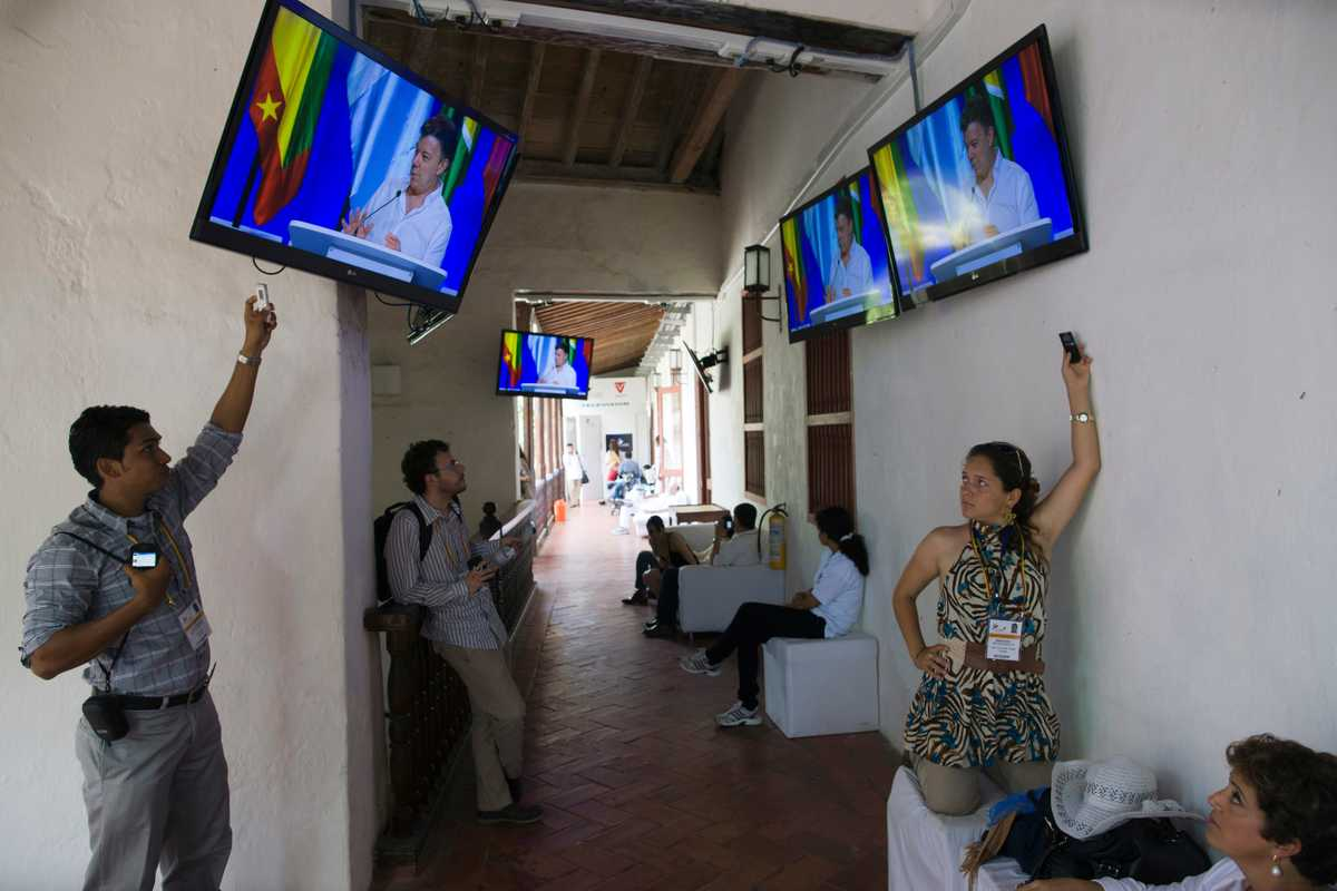 Screens locked to President Santos's summit speech