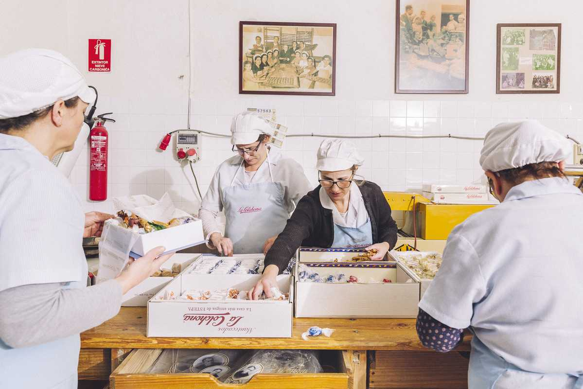 'Mantecado' sweets being individually wrapped and arranged into presentation boxes at the La Colchona factory