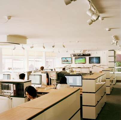 The Monocle office has oak-topped desks and shelving by Novex, Tolomeo task lamps by Artemide and carpets by Tisca Tiara. Panasonic televisions keep staff updated with breaking news. Walls of original windows on both sides of the office provide plenty of daylight and a through draft when open