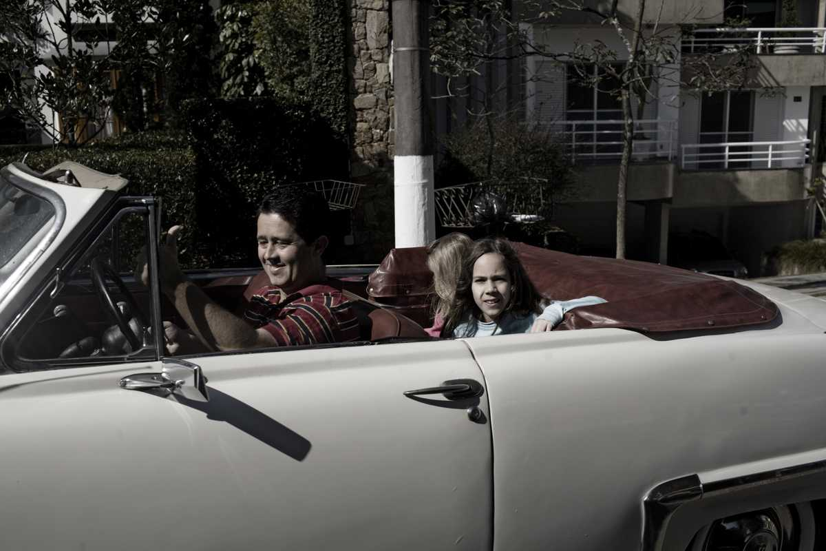 A father drives his family in a 1950s Plymouth car