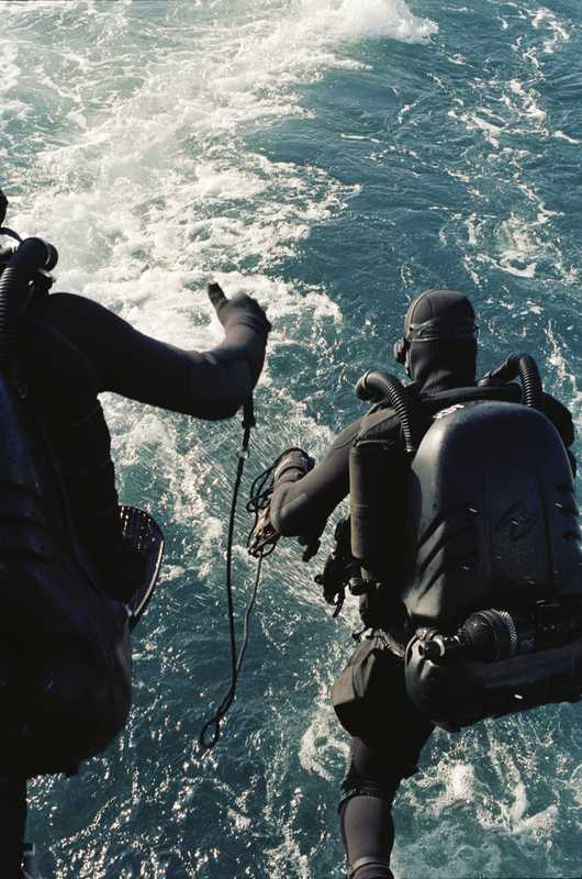 Sailors jumping into the sea to disarm a mock bomb