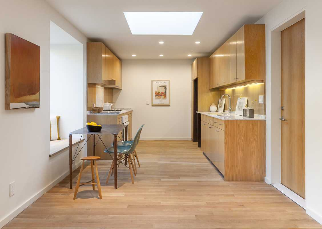 White-oak cabinets are treated simply; throughout to let light into the compact spaces