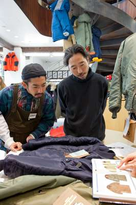 Shop staff learning about vintage aviation jackets