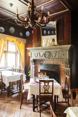 Tuscan fireplace and wooden chandelier in dining room