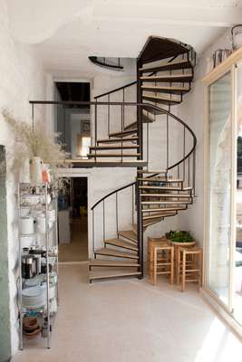 Modern circular stairs lead up to the top floor