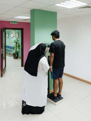 Patient's weight being measured at the Qatar Diabetes Association