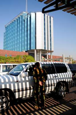 Security men and SUVs outside the International Hotel