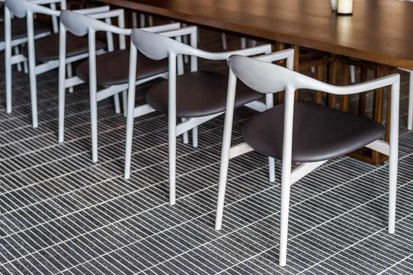 Jari dining chairs in private dining room by OEO for Brdr Krüger; brick-tile flooring by Kunishiro