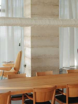 Dining area with chairs from the Horgen Glarus collection and a table designed by Peter Zumthor