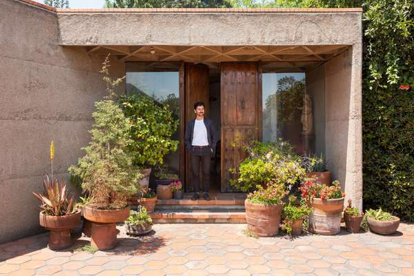 Carlos H Matos at the home's plant-laden entrance
