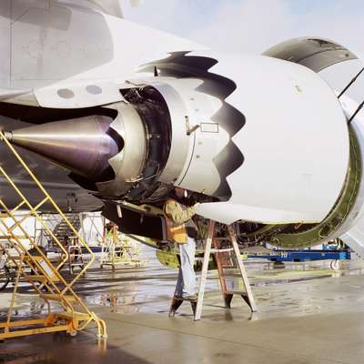 A technician works on a GEnx-2B engine of a nearly completed 747-8 on the flight line