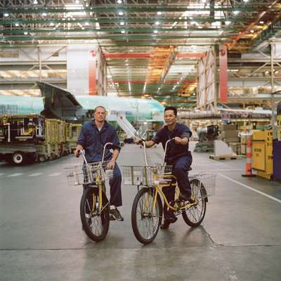 Shad Talbot (left) and Son Ho ride bikes through the Boeing facility