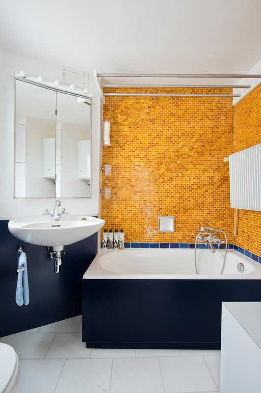 Orange ceramic glass tiles in the bathroom have a 1960s feel