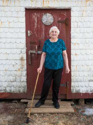 A resident of Barr'd Islands community outside her husband's shed
