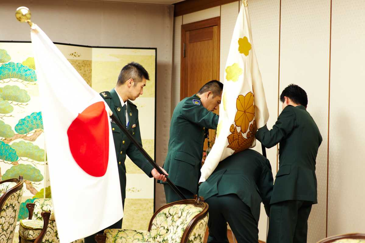GSDF staff setting up the meeting room with flags