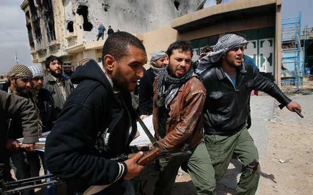 Libyan rebel fighters carrying a wounded comrade in Misurata