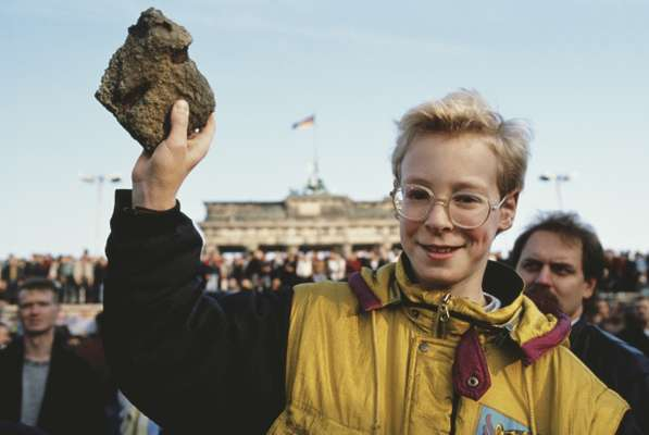 10 November 1989: a bystander holds a souvenir chunk of masonry from the Berlin Wall the day after it fell