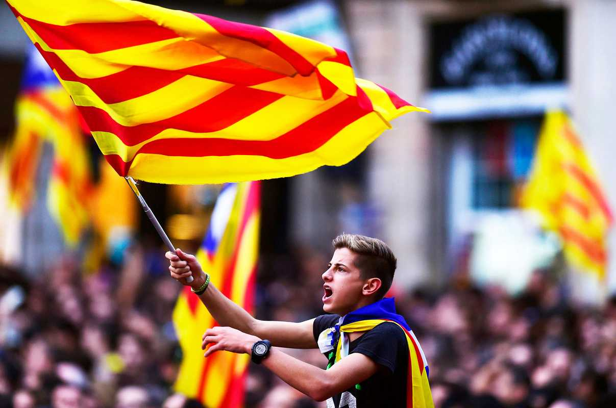 A boy waves a flag as people celebrate Catalonia's parliamentary vote to declare independence