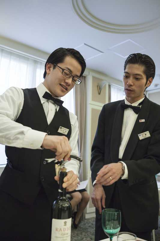 Instructor Shinji Ueno (right) showing a student how to use a cockscrew