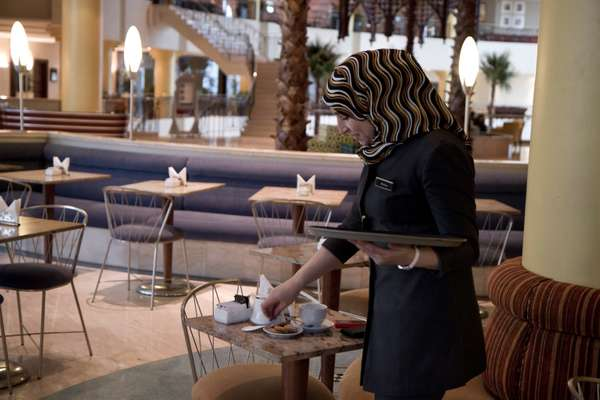 Malika serving coffee and cookies in the lobby café