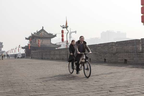 Tourists and locals ride bikes around Xi'an's ancient city wall