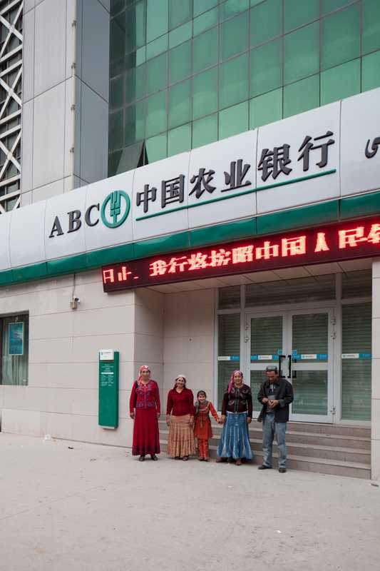 Uyghur family by a bank in downtown Kashgar