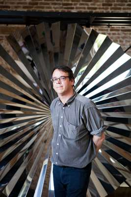 Andrew Ignarski stands in front of an Anish Kapoor work