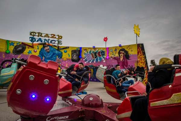 Young couples enjoying a ride at a newly reopened theme park, East Mosul