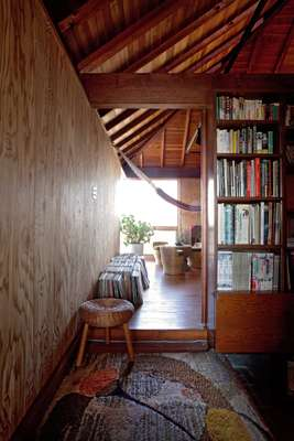 Second floor: Second floor, at the top of the stairs is a 1950s rug and rattan school. A bookshelf doubles as a partition.