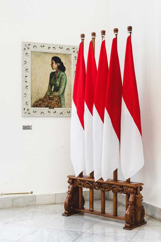 Sang Saka Merah-Putih (lofty red-and-white) flags with one of the palace's many paintings