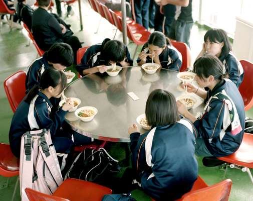 Students eat udon noodles on the ferry to Sakurajima