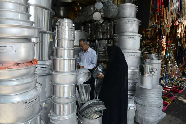 A woman in a black 'chador' in a shop selling aluminium goods