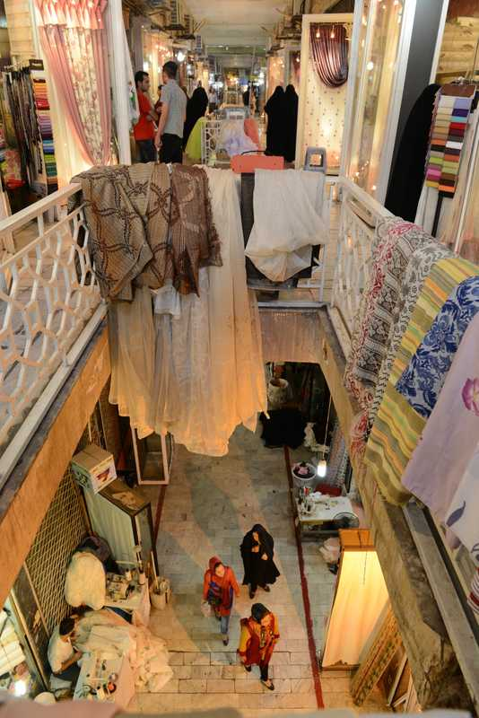 People browsing a curtain fabrics market