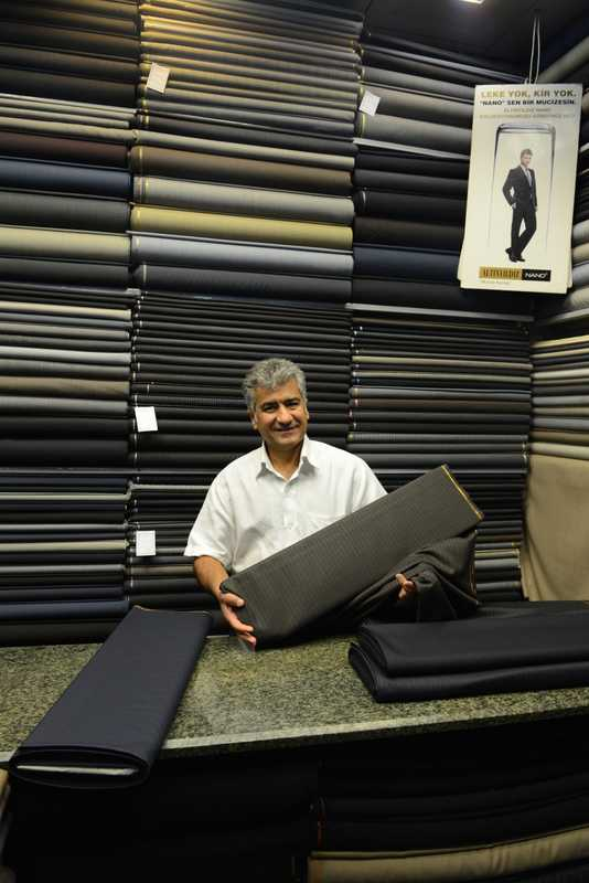 Mohammad Rezai stands in his small shop selling fabrics for men's suits