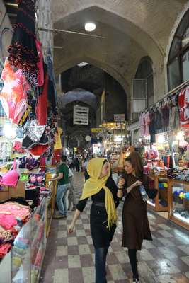 Two women walk past colourful underwear in the Grand Bazaar