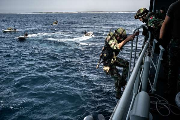 Marines scramble down ladders from the 'Bérrio' to small inflatable craft as they take part in a beach-landing exercise