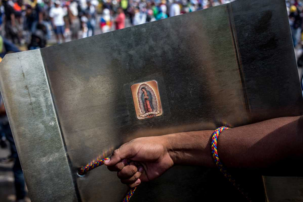 Virgin Mary stamp on a shield used in an anti-government protest
