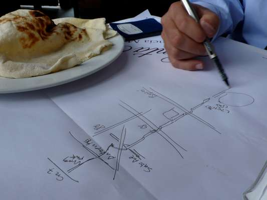The former mayor sketches a map of Bogotá's bike routes on a paper table setting