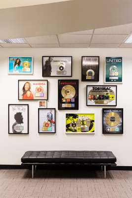 Gold and platinum discs on the wall at CCMG headquarters