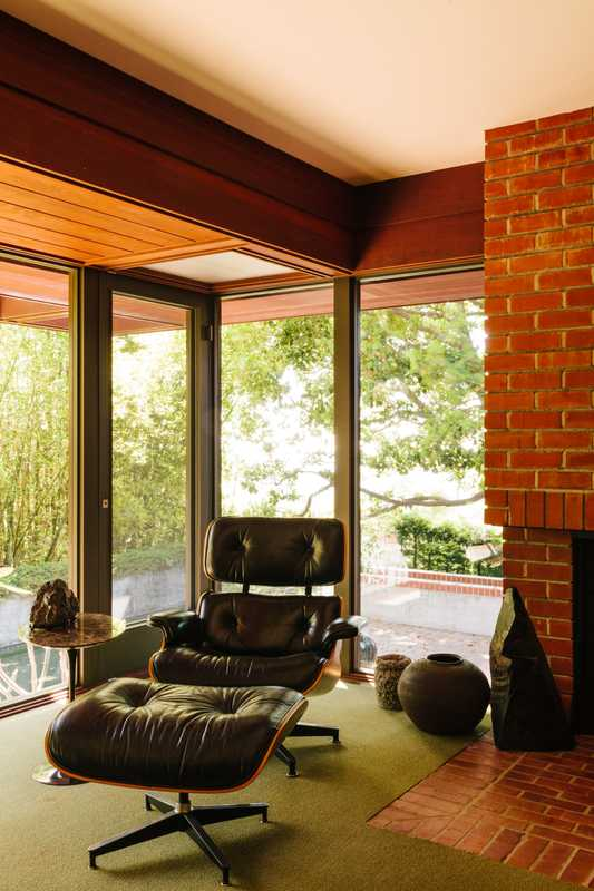 Vintage Eames Lounge Chair beside the indoor-outdoor fireplace in the study