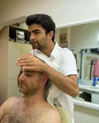 Simsek providing the traditional post-haircut head-and-shoulder rub