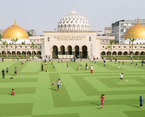 Families relax in the renovated Alun-Alun Park located behind Bandung's Grand Mosque