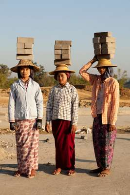 Construction workers balancing bricks on their heads