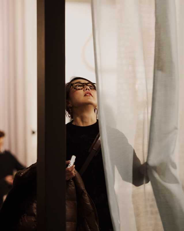 Visitor looking at curtains at IMM Cologne